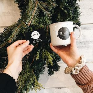 two hands holding a local cafes branded mug and business card