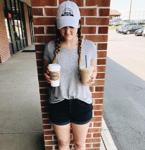 young lady holding 2 coffee beverages outside of a local coffee company