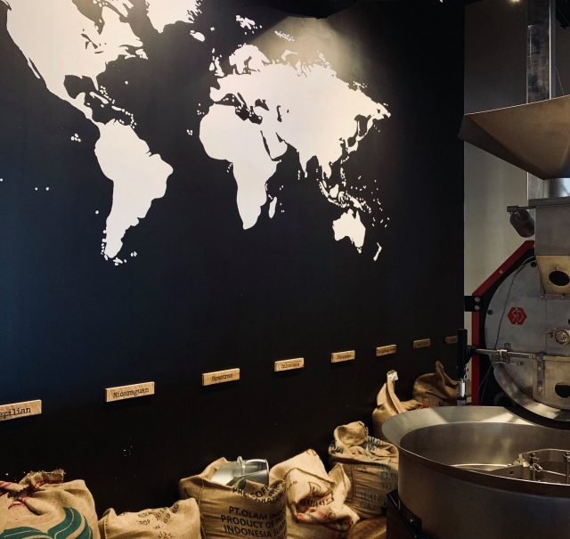 world map behind a coffee shop counter