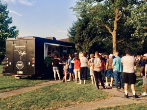 customers waiting in a long line outside of coffee and food truck